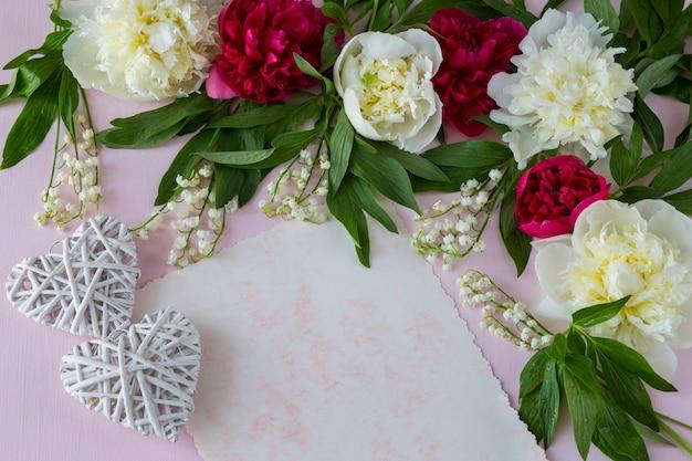 Em um fundo rosa peônias e lírios do vale, uma folha de papel e dois corações brancas