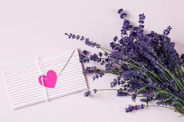 Em um fundo rosa um buquê de lavanda e um envelope de carta com um coração