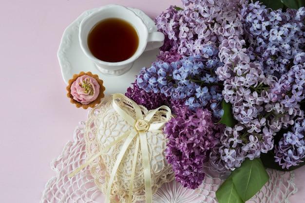 Em um fundo rosa um buquê de lilás, uma xícara de chá, um bolo e um coração feito de rendas