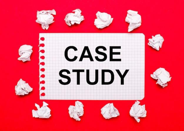 Em um fundo vermelho brilhante, folhas de papel branco amassadas e uma folha de papel com o texto estudo de caso