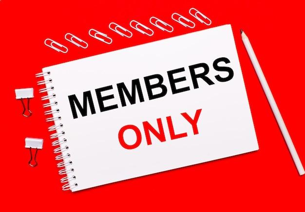 Em um fundo vermelho brilhante, um lápis branco, clipes de papel brancos e um caderno branco com o texto somente membros.