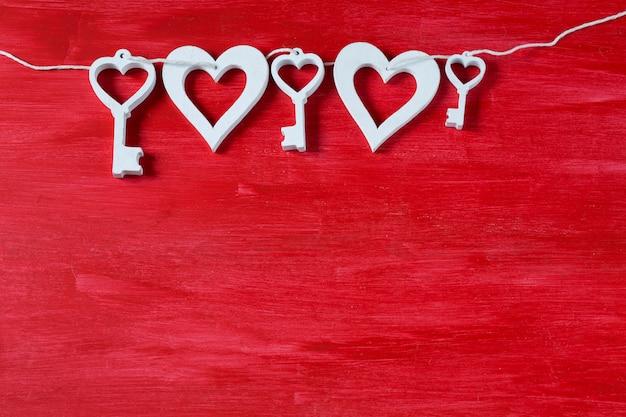 Em um fundo vermelho de madeira chaves decorativas e corações de cor branca, feitos de madeira