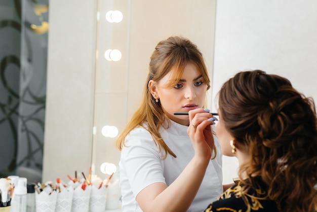 Em um lindo e moderno salão de beleza, um estilista de maquiagem profissional faz maquiagem para uma jovem. beleza e moda.