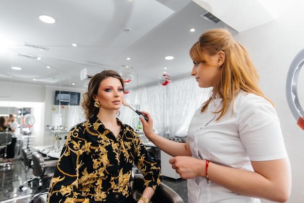 Em um lindo e moderno salão de beleza, um estilista de maquiagem profissional faz maquiagem para uma jovem.