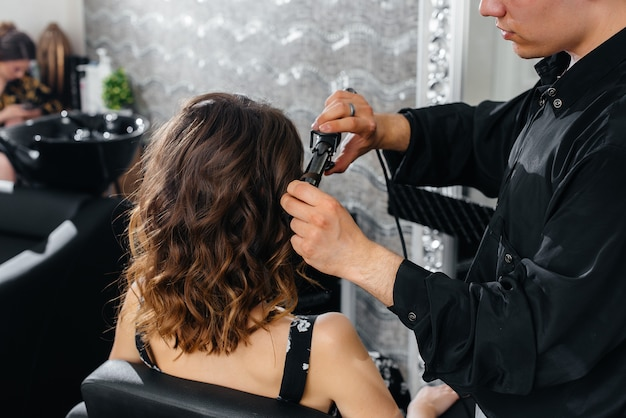 Em um lindo e moderno salão de beleza, um estilista profissional faz um corte de cabelo e penteado para uma jovem. beleza e moda.