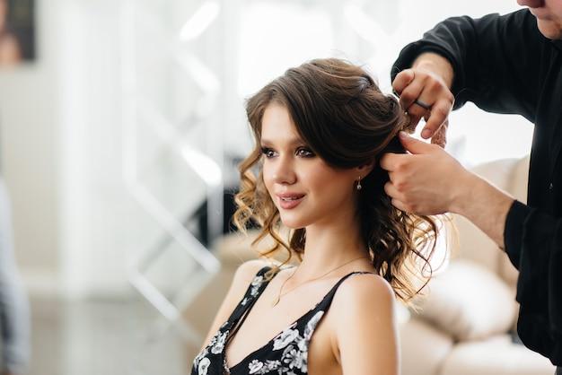 Em um lindo e moderno salão de beleza, um estilista profissional faz um corte de cabelo e penteado para uma jovem