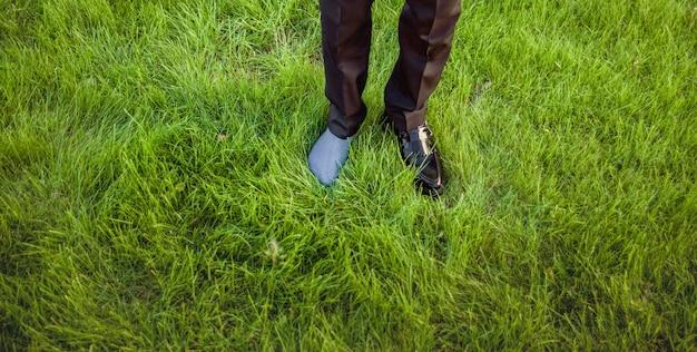 Em um pé tem um sapato, o outro pé usando meias