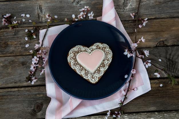 Em um prato azul de gengibre em forma de coração e floração ramo de cereja