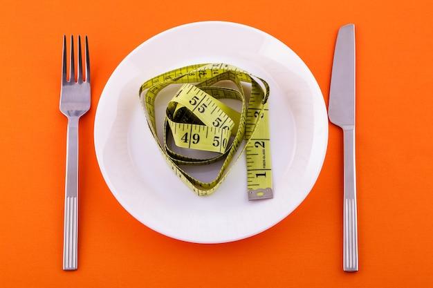 Em um prato branco encontra-se uma fita métrica amarela, uma faca com um garfo em uma superfície laranja de perda de peso e conceito de dieta