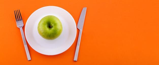 Em um prato branco encontra-se uma maçã verde, uma faca com um garfo em uma vista de fundo laranja do topo di ...