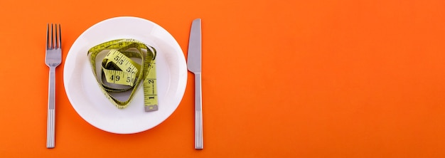 Em um prato branco está uma fita métrica amarela, uma faca com um garfo em um fundo laranja