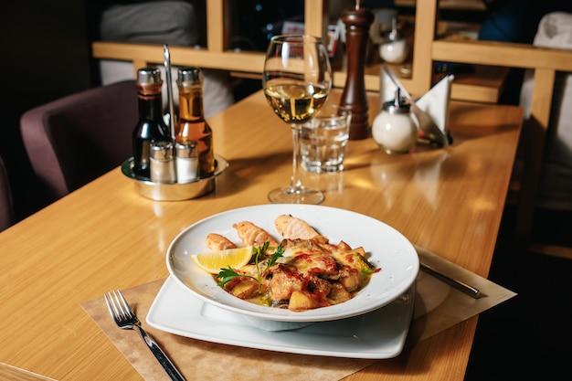 Em um prato branco, salmão assado, batatas assadas e queijo.