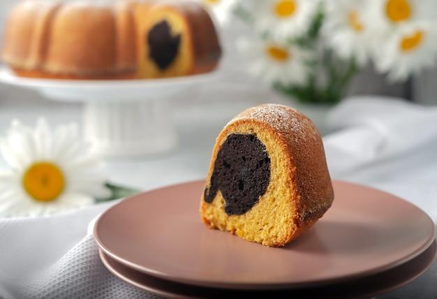 Em um prato branco, um cupcake redondo, redondo com furo, polvilhado com açúcar de confeiteiro