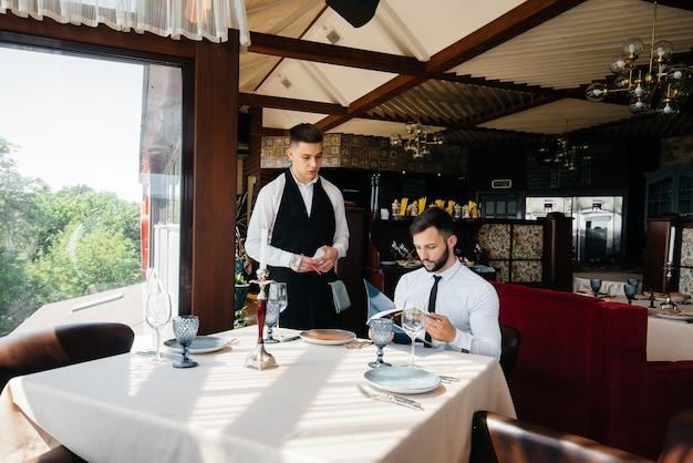 Em um restaurante sofisticado, um jovem empresário examina o cardápio e faz um pedido para um jovem garçom com um avental estiloso. atendimento ao cliente.