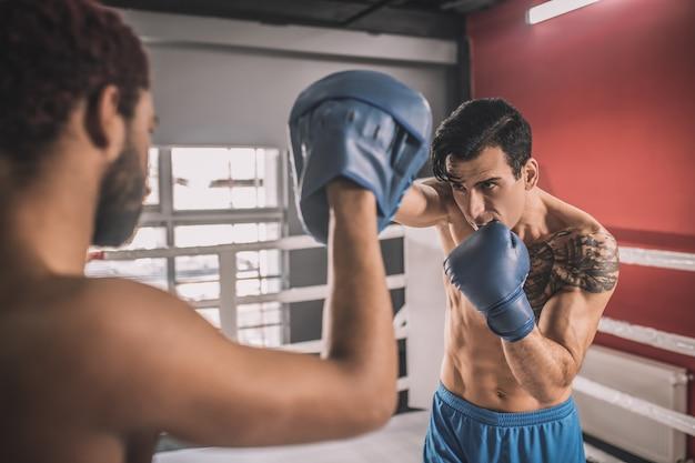 Em um ringue de boxe. kickboxers lutando em um ringue de boxe e parecendo envolvidos