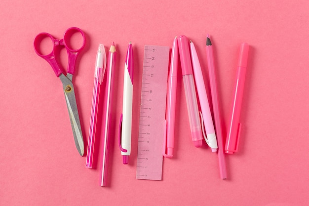 Em um rosa, acessórios de escola e uma caneta, lápis de cor