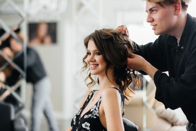 Em um salão de beleza bonito e moderno, uma estilista profissional faz um corte de cabelo e penteado para uma jovem garota. beleza e moda.