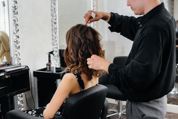 Em um salão de beleza bonito e moderno, uma estilista profissional faz um corte de cabelo e penteado para uma jovem garota.