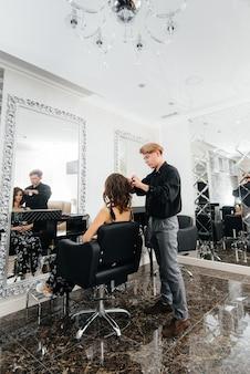 Em um salão de beleza moderno, um estilista profissional faz um corte de cabelo e penteado para uma jovem
