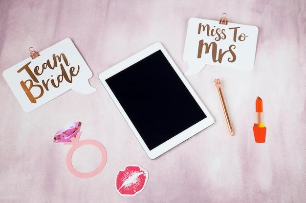 Em um tablet de fundo rosa, anel, caneta, beijo, batom - planejando uma festa de despedida de solteira, casamento