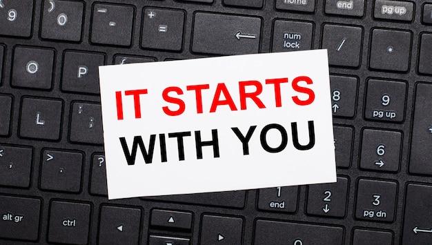 Em um teclado de computador preto, há um cartão branco com o texto começa com você. vista de cima