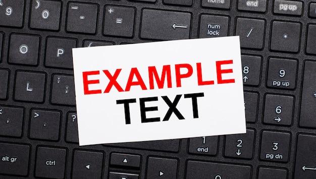 Em um teclado preto de computador, há um cartão branco com o texto exemplo de texto