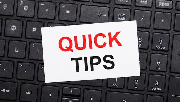 Em um teclado preto de computador, há um cartão branco com o texto quick tips. vista de cima