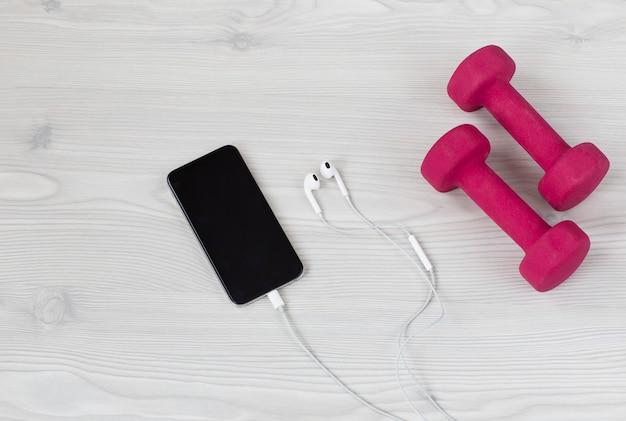 Em um telefone celular de luz de fundo, fones de ouvido e halteres