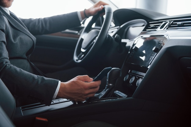 Em um terno preto clássico. empresário moderno experimentando seu novo carro no salão automóvel.