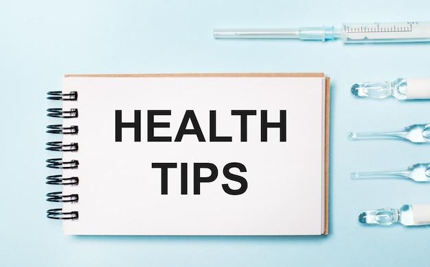 Em uma ampola de fundo azul com medicamentos e um caderno com o texto dicas de saúde. conceito médico