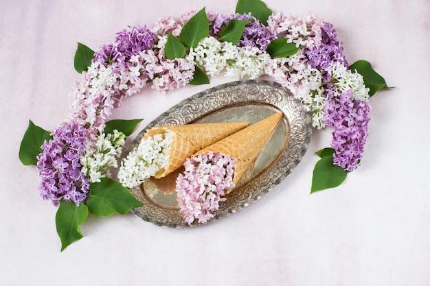 Em uma antiga placa de prata, dois cones de sorvete de bolacha e um ramo lilás