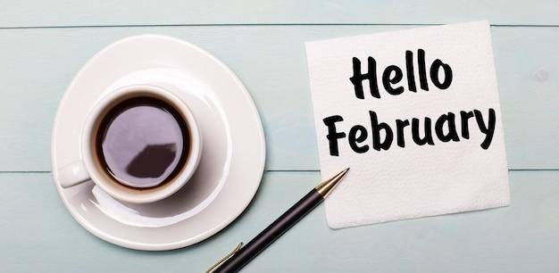 Em uma bandeja de madeira azul clara, há uma xícara de café branca, uma alça e um guardanapo que diz olá fevereiro