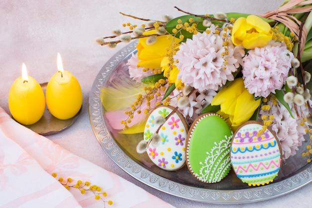 Em uma bandeja de prata, um buquê de jacintos e tulipas, duas velas em forma de ovos, penas e um pão de gengibre em forma de ovos