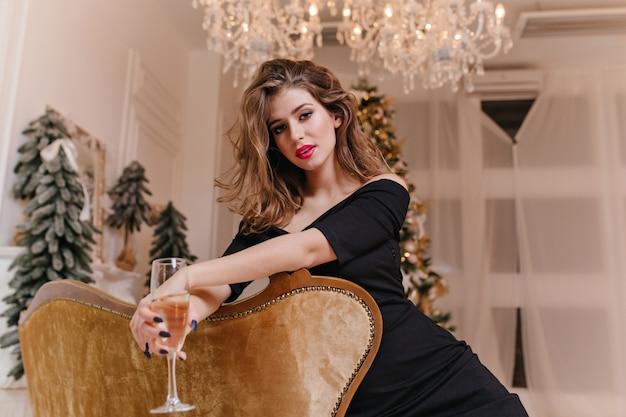Em uma bela sala de design com janelas panorâmicas e lustre de cristal, uma mulher muito bonita está sentada no sofá dourado, segurando uma taça de vinho espumante