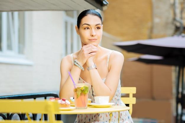 Em uma cafeteria. mulher jovem e bonita calma, sentada confortavelmente à mesa no terraço de um café e olhando para longe enquanto espera por um amigo