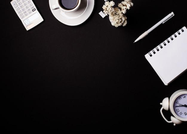 Em uma calculadora de fundo preto, bloco de notas, despertador, flores, café e uma caneta. copie o espaço.
