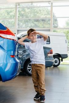Em uma concessionária de automóveis, um menino feliz fica perto de um carro novo antes de comprá-lo