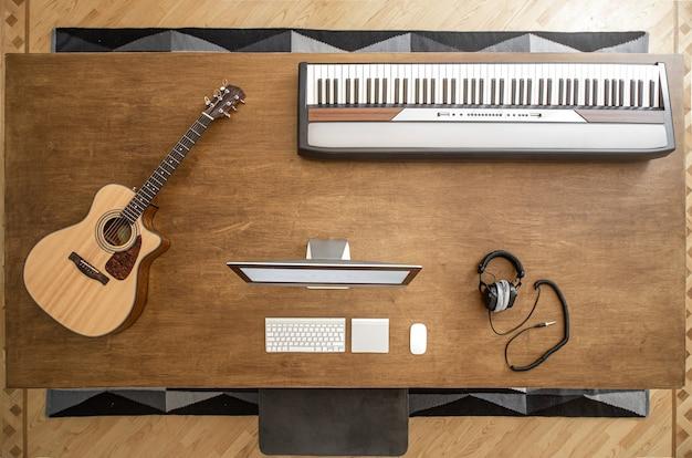 Em uma grande mesa de madeira, há um computador fixo, teclas musicais e fones de ouvido de estúdio para gravação de som.
