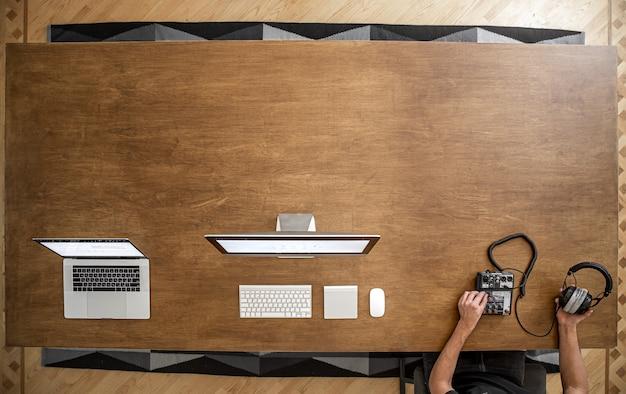 Em uma grande mesa de madeira há um laptop, um computador, mãos masculinas com um mixer de som e fones de ouvido.