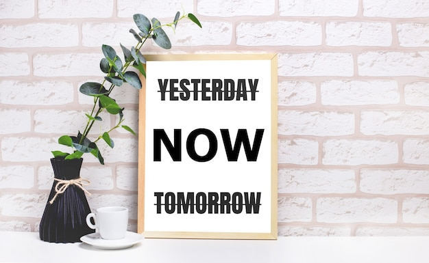 Em uma mesa branca contra uma parede de tijolos claros, um galho de eucalipto em um vaso escuro, uma xícara branca e uma moldura de madeira clara com o texto ontem, agora amanhã. interior do escritório em casa.
