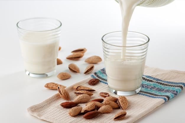Em uma mesa branca de leite de amêndoa em um copo com amêndoas
