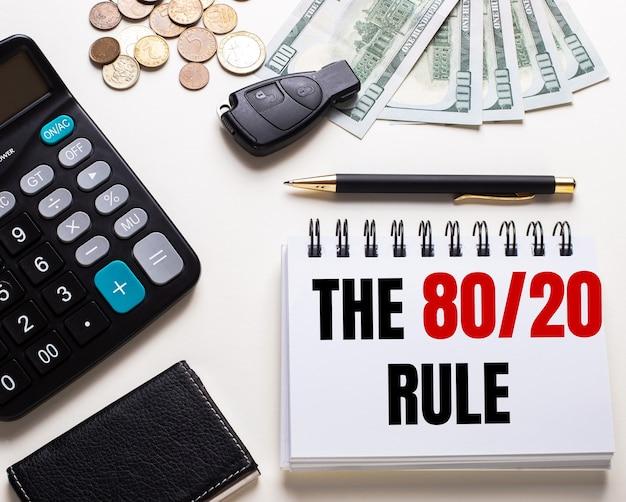 Em uma mesa branca está uma calculadora, a chave do carro, dinheiro, uma caneta e um caderno com a inscrição the 80 20 rule