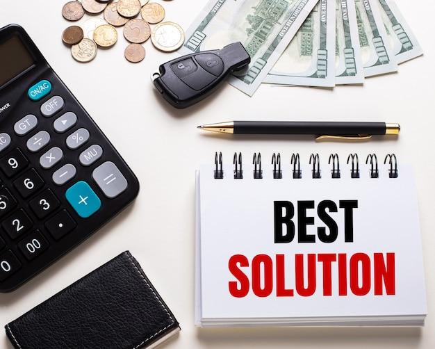 Em uma mesa branca está uma calculadora, chave do carro, dinheiro, uma caneta e um caderno com a inscrição melhor solução