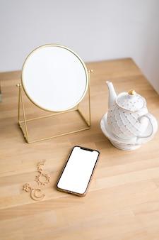 Em uma mesa branca há uma xícara de café, telefone mock up e mirrow. foto de alta qualidade