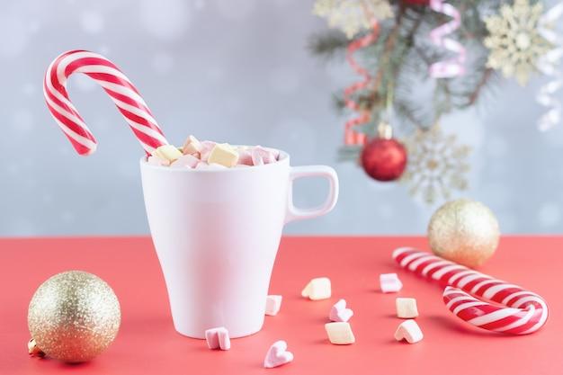 Em uma mesa branca marshmallows em uma xícara com café com leite