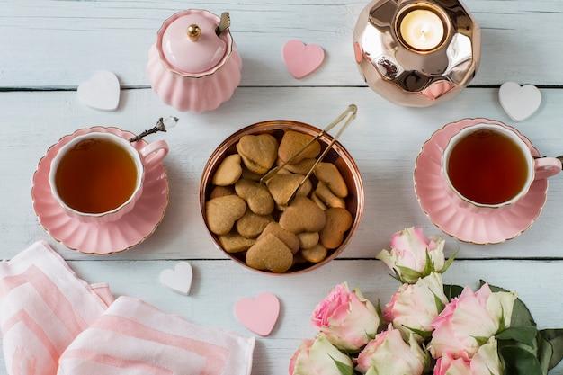 Em uma mesa branca rosas cor de rosa, chá em xícaras cor de rosa, bolos, doces, corações decoração de tecido, açúcar