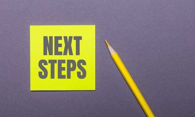 Em uma mesa cinza, um lápis amarelo brilhante e um adesivo amarelo com as palavras próximas etapas