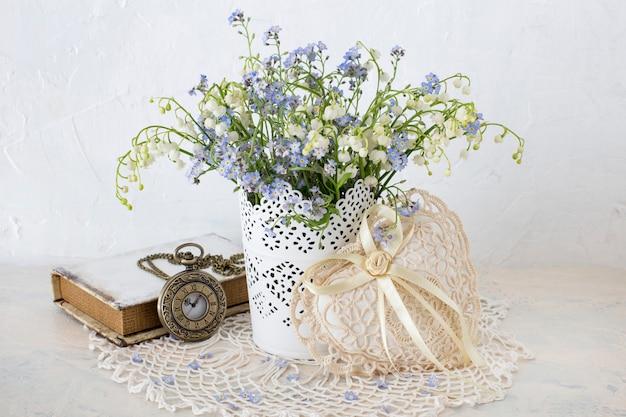 Em uma mesa de luz, esqueça-me nots e lírios do vale são colocados em um vaso, um livro, um coração