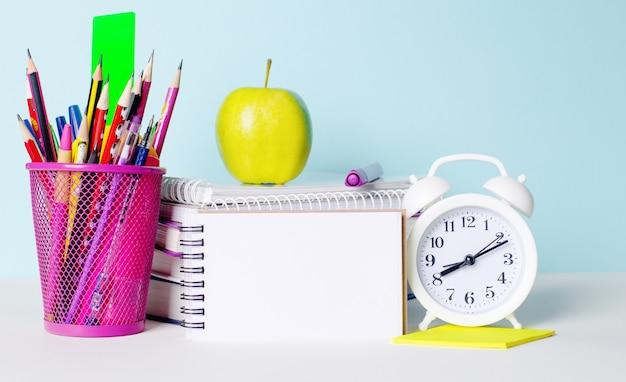 Em uma mesa de luz estão livros, artigos de papelaria, um despertador branco, uma maçã. ao lado de um caderno em branco com um local para inserir texto