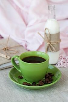 Em uma mesa de luz, há uma xícara de café e uma garrafa de leite. em seguida é um caderno de artesanato e um guardanapo rosa.